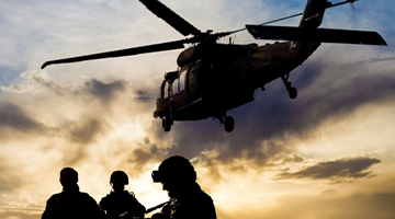 three soldiers with a helicopter flying overhead