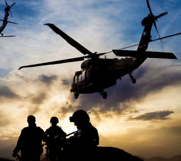 Three soldiers and a helicopter overhead
